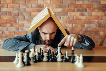 Male chess player with board on his head