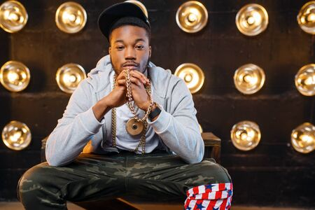 Black rapper in cap poses, perfomance on stage Фото со стока