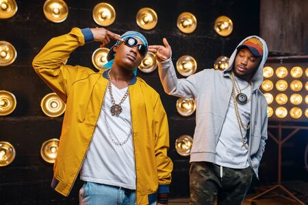 Two black rappers in caps, artists poses on stage Stock Photo