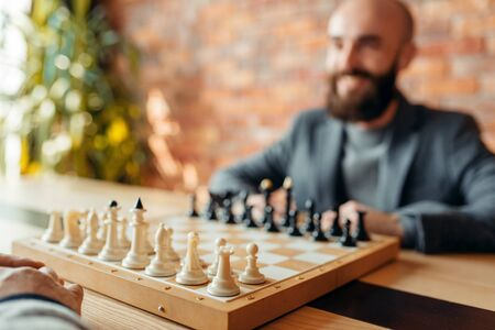 Male chess players, focus on board with figures