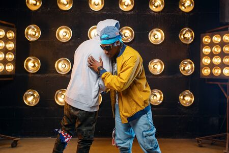 Two black rappers in caps hugging on stage