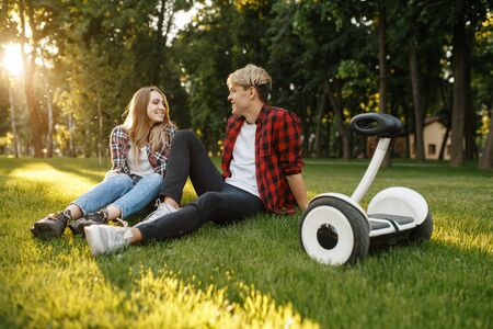 Young couple sitting on the grass near gyro board