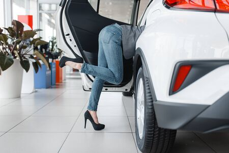 Womans sticking out of new car in showroom