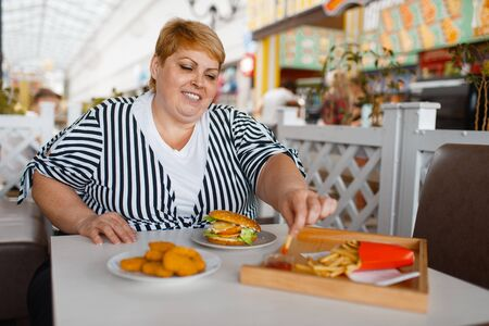 Fat woman eating french fries in mall food court