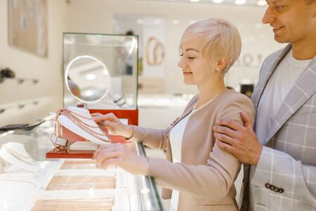 Love couple choosing gold chain in jewelry store