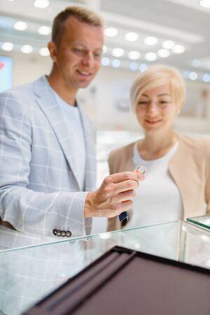 Love couple choosing wedding rings, jewellery shop