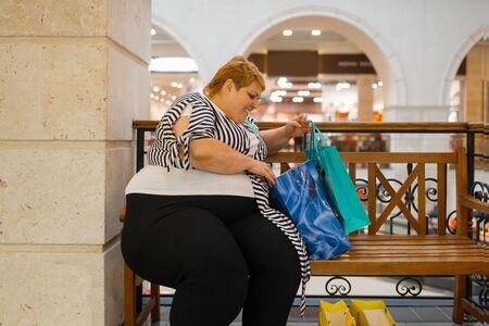 Mujer gorda con bolsas de compras sentado en el banquillo Foto de archivo