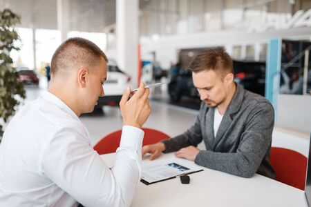 Manager and buyer make out the purchase of new car 写真素材