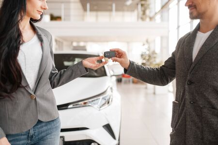 Couple buying new car, man gives the key to woman