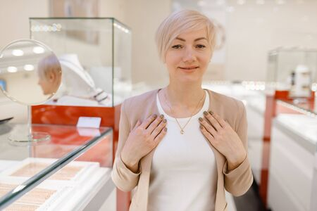 Woman trying on golden necklace in jewelry store