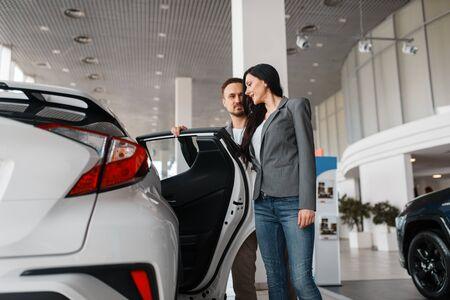 Couple choosing new car in showroom