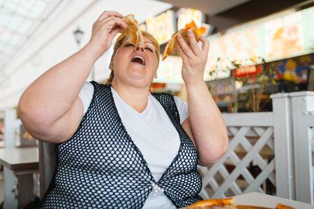 Fette Frau, die Pizza isst, ungesundes Essen
