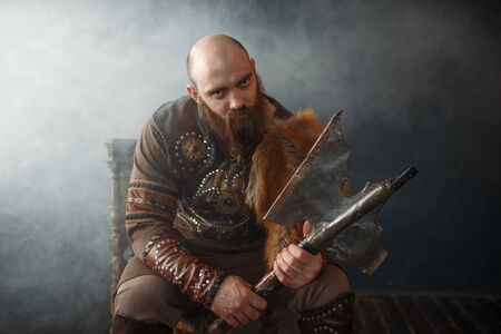 Bearded viking with axe sitting on chair