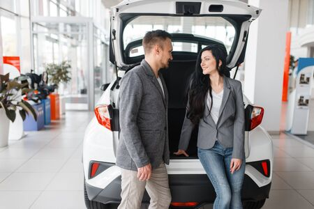 Couple buying car, man and woman near the trunk