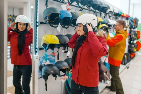 Woman trying on helmet at the mirror, sports shop