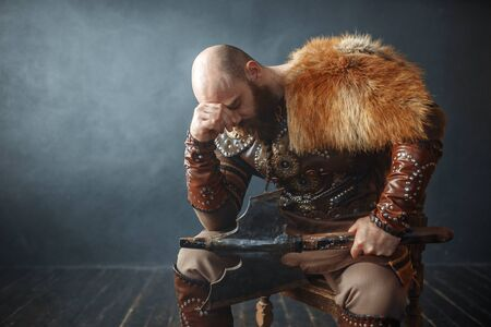 Sad viking with axe sitting on chair Reklamní fotografie