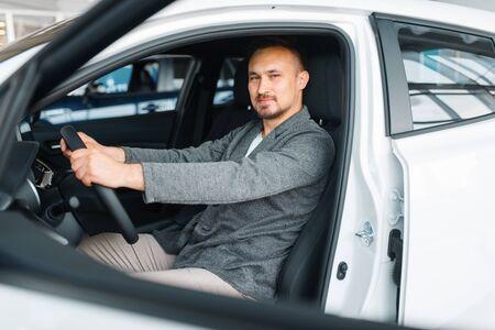 Man sitting in new car, showroom