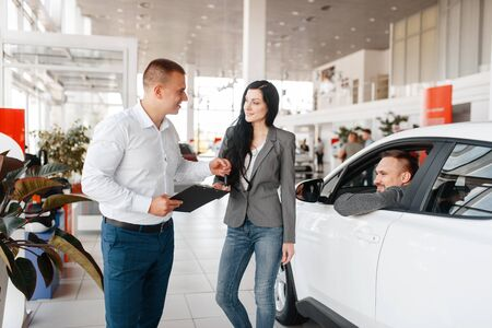 Manager and couple near the new car in showroom