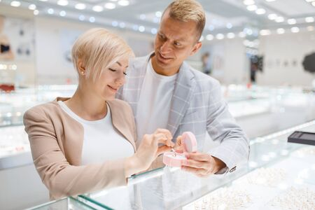 Couple buying gold decoration in jewellery shop