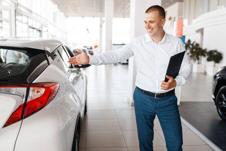 Salesman shows new car in showroom 写真素材