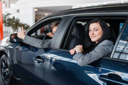 Heureux couple assis dans une nouvelle voiture, salle d'exposition