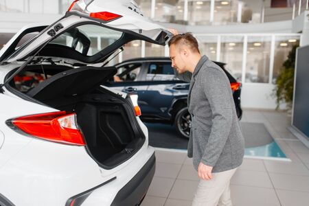 Man looks at the trunk of new car in showroom 写真素材