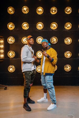 Two black rappers in caps, artists poses on stage Imagens