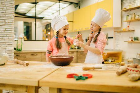 Little girls cooks in caps tastes vanilla powder