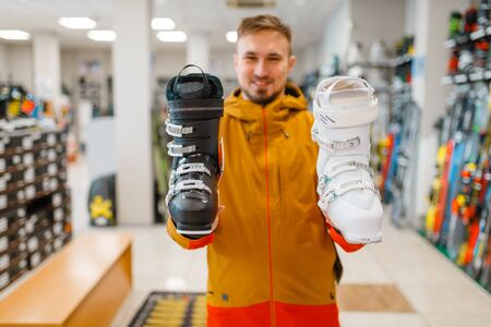 Man shows ski or snowboarding boots in sports shop Banco de Imagens