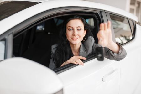 Happy woman shows key to the new car in showroom
