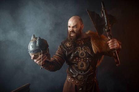 Angry viking holds enemys skull in helmet and axe