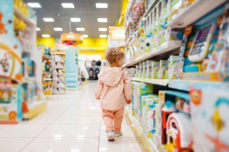 Kleines Mädchen, das Spielzeug im Kinderladen wählt Standard-Bild
