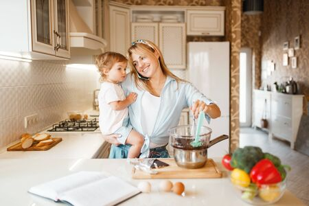 Mother and daughter prepares pastry with chocolate Stock Photo