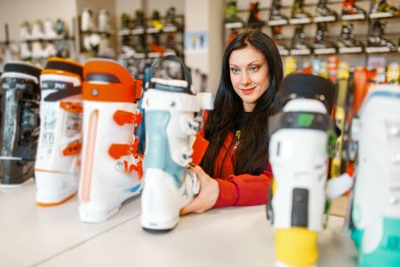Female person choosing ski or snowboarding boots