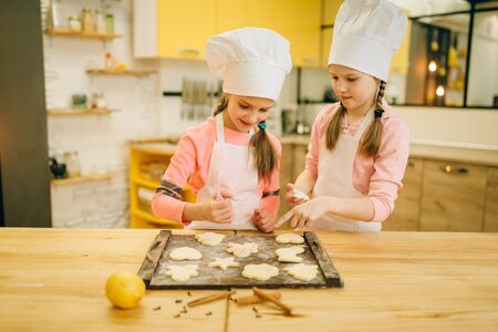 Two little girls cooks spread out cookies on board