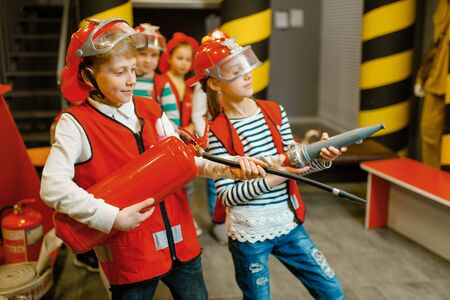 Children with hose and extinguisher, little heroes Banco de Imagens
