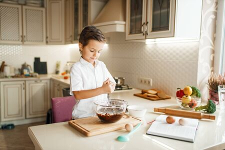 Young boy mixing melted chocolate in a bowl