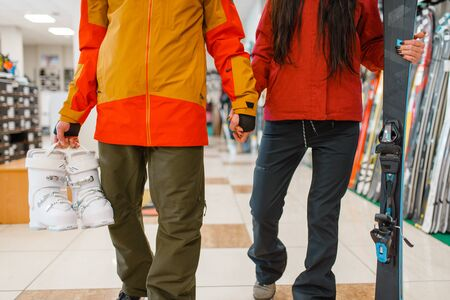 Couple with skis and boots in hands, sports shop