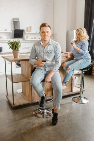Young love couple drinks wine on the kitchen Stock Photo
