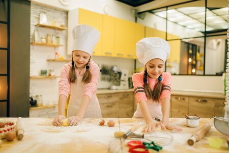 Little girls chefs crumple the dough, funny bakers
