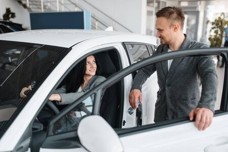 Couple buying new car, woman behind the wheel