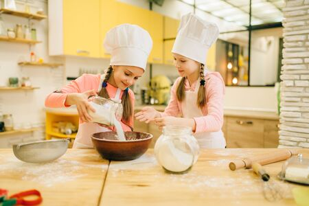 Little sisters cooks in caps pours flour in a bowl Stok Fotoğraf