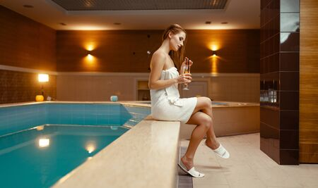 Woman in towel on the body drinks tea at the pool Banque d'images - 129829038