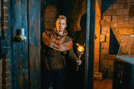 Traveler with torch in hand wandering the maze