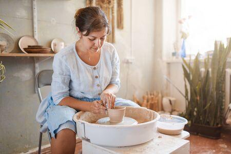 Female master making a pot on pottery wheel Stockfoto