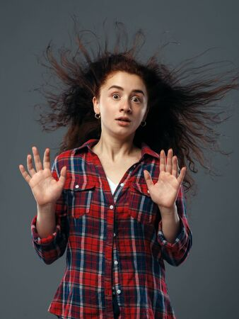 Strong fan blowing in female face, funny emotion Stock Photo