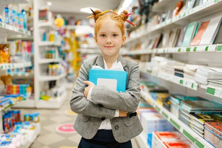 Klein schoolmeisje in kantoorboekhandel Stockfoto
