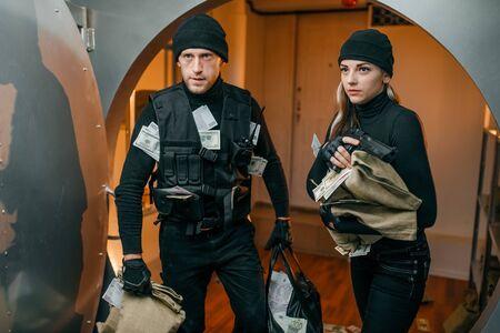 Ladrón en uniforme negro tiene bolsas llenas de dinero