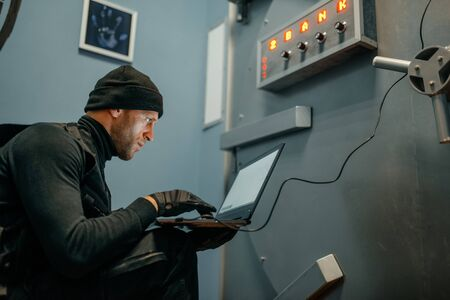 Robber with laptop trying to open the vault door