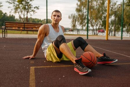 Basketball player with ball sitting on the ground